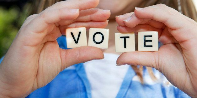 Young girl holding small block letters with message: Vote