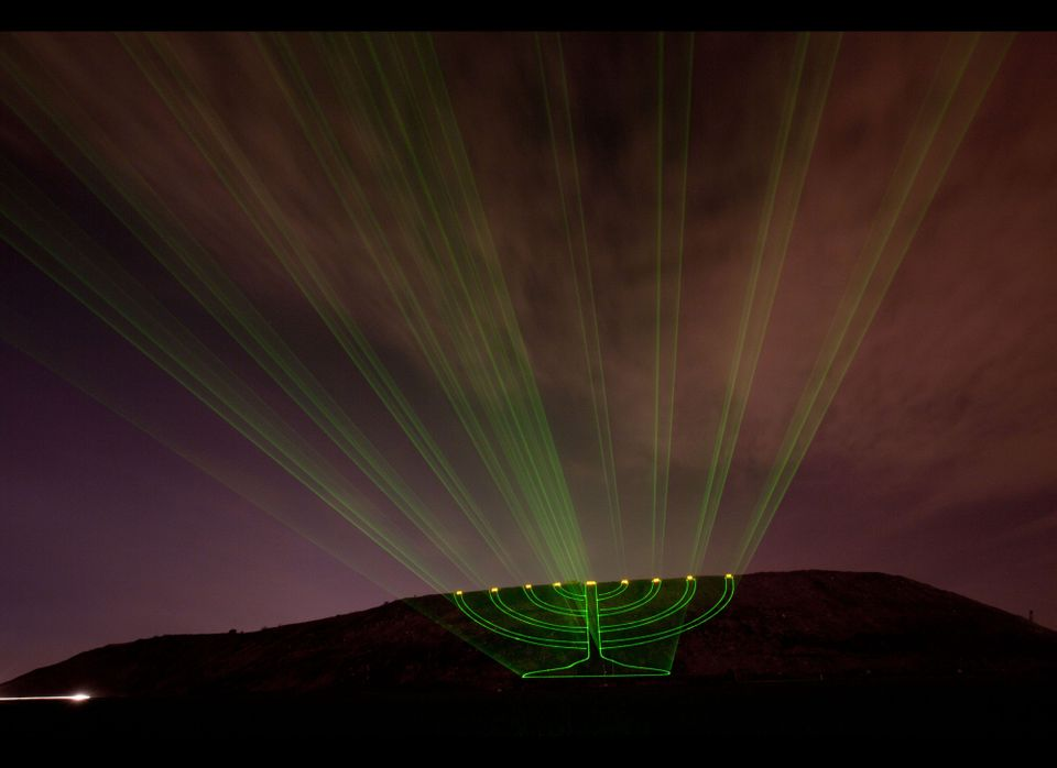 Laser beams creating the image of a large lit Hanukkah menorah are projected on the Hiriya landfill, a former waste disposal