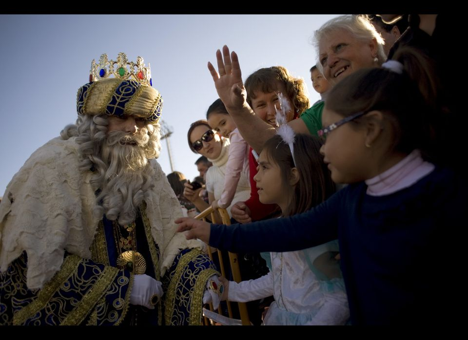 A men dressed as King Melchior meets children upon his arrival with men dressed as Kings Balthazar and Melchior, otherwise kn