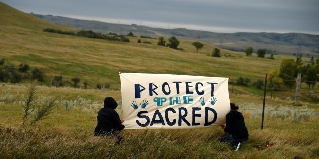 People hang a sign near a burial ground sacred site that was disturbed by bulldozers building the Dakota Access Pipeline (DAP