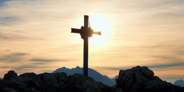 Iron cross at mountain top in alp. Cross on top of a mountains peak as typical in the Alps. Monument to the dead climbers