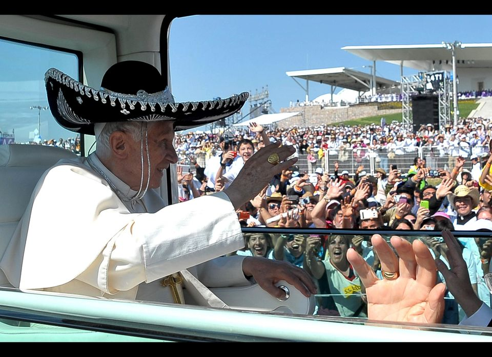 Pope Benedict XVI waves from the popemobile wearing a Mexican sombrero as he arrives to give a Mass in Bicentennial Park near