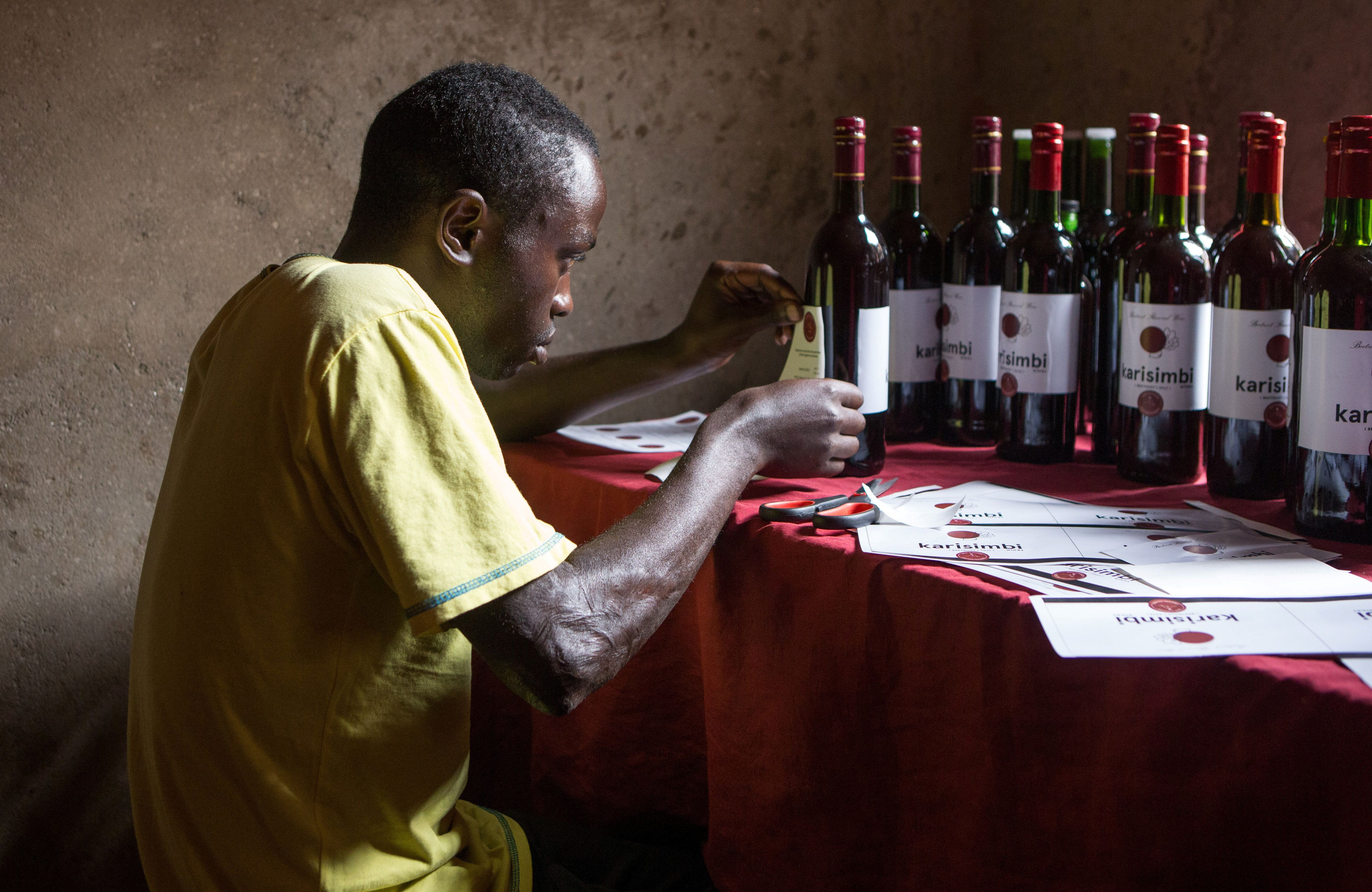 A worker labels bottles of wine from the juice of beetroot at a production stall in Rubavu district, Western province, Rwanda October 3, 2018. Pictures taken October 3, 2018. REUTERS/Jean Bizimana