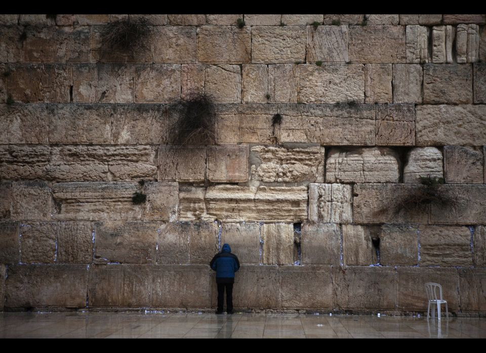 A man prays on a rainy morning by the Western Wall in the Old City of Jerusalem, Friday, Jan. 13, 2012. The Western Wall is i
