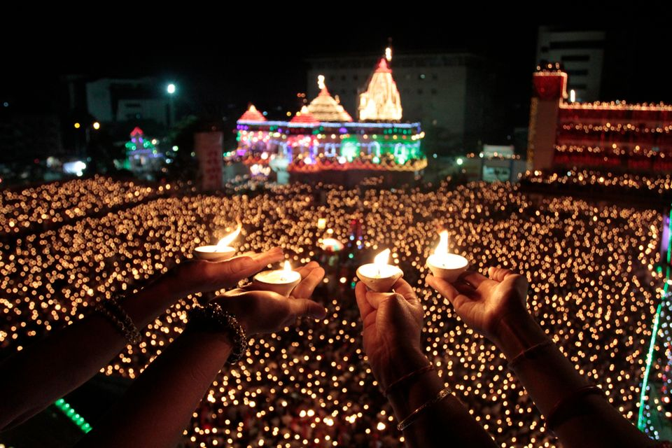 Indian devotees holds earthen lamps and take part in Maha Aarti ritual at Hindu deity Umiya Mata temple on the eighth night o
