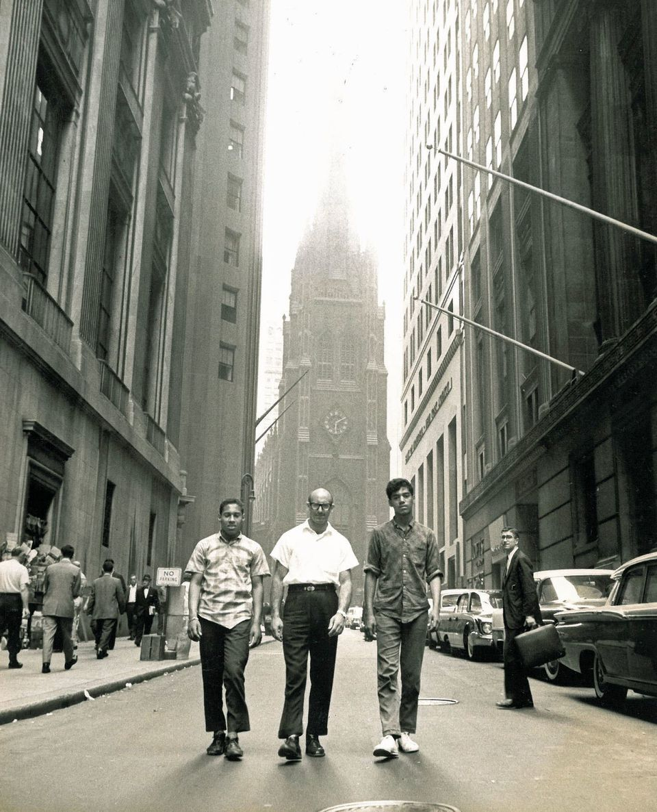 Early 1960s. Vinnie DiPasquale and two kids he was ministering to. They're walking down Wall Street, NYC. Behind them is Trin