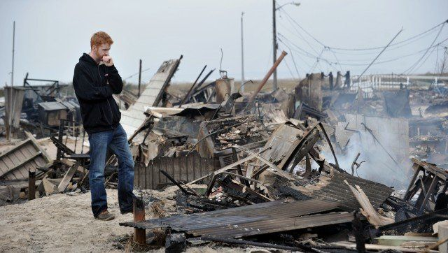 Gavin Byrne views damage in the Breezy Point area of Queens in New York on October 30, 2012 after fire destroyed about 80 hom