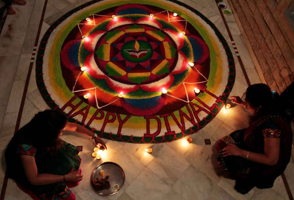 Members of a Hindu family place earthen lamps on near rangoli, a hand decorated pattern on the floor, ahead of the upcoming f