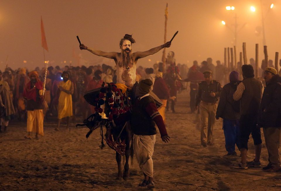 A horse mount naked Hindu holy man or a Naga Sadhu beats the drum as he returns after a dip at Sangam, the confluence of the
