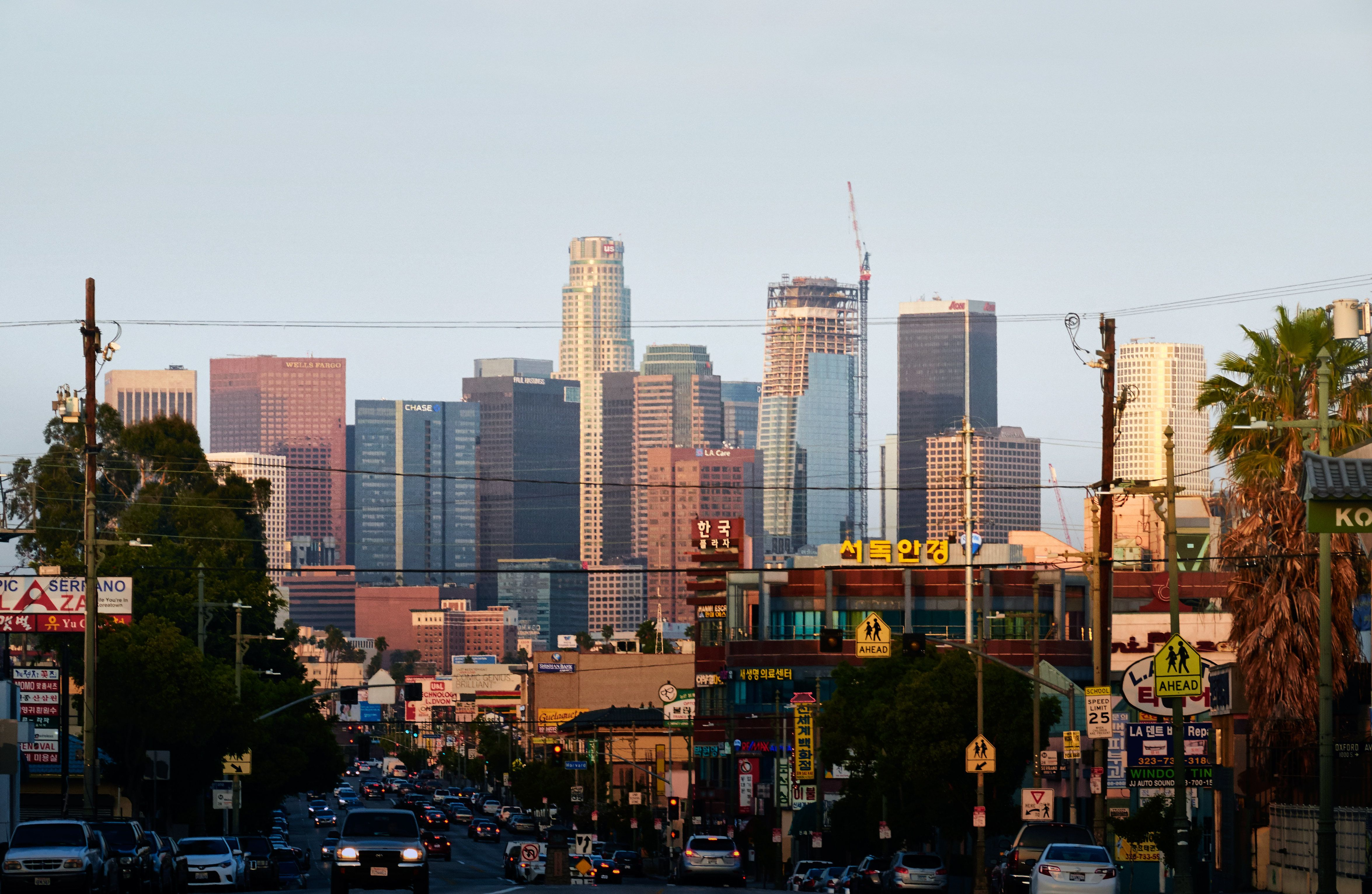 As the sun rises across downtown Los Angeles, commuters on a section of Olympic Blvd in Koreatown are cast in shadow