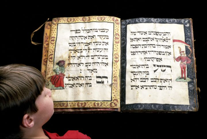 Child studies ancient handwritten Haggadah