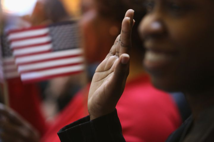 NEW YORK, NY - MARCH 22:  Immigrants raise their hands for the oath of allegiance to the United States to become American cit