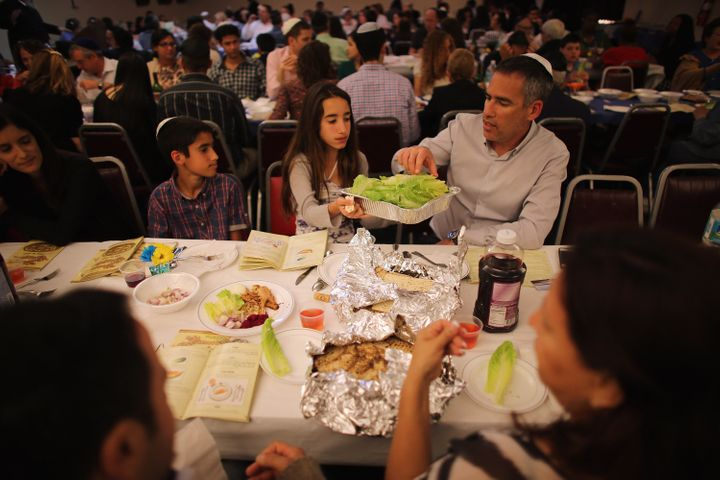 MIAMI BEACH, FL - MARCH 25:  Omri Brandes, Nitzan Brandes and Bentsi Brandes (L-R) eat during a  community Passover Seder at