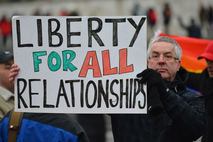 A protester holds up a placard that reads 'Liberty for all relationships' as he joins a demonstration for equal rights for ga