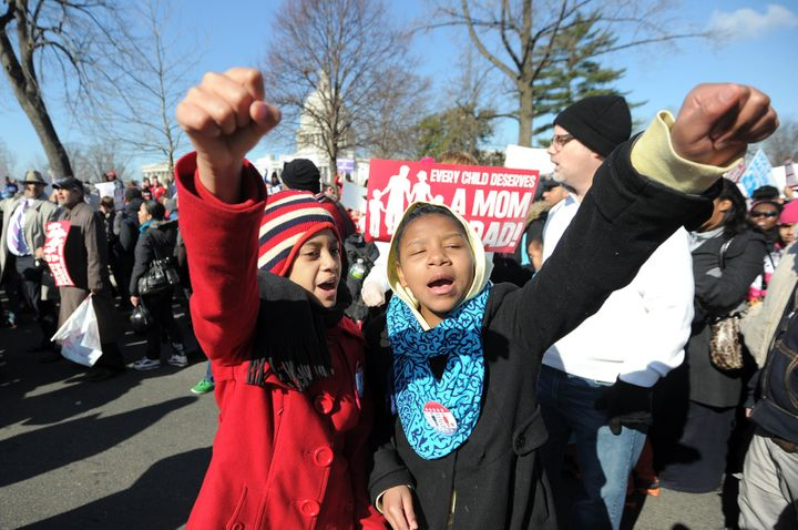 Two young girls shout slogans as they join anti same-sex marriage supporters in front of the US Supreme Court on March 26, 20