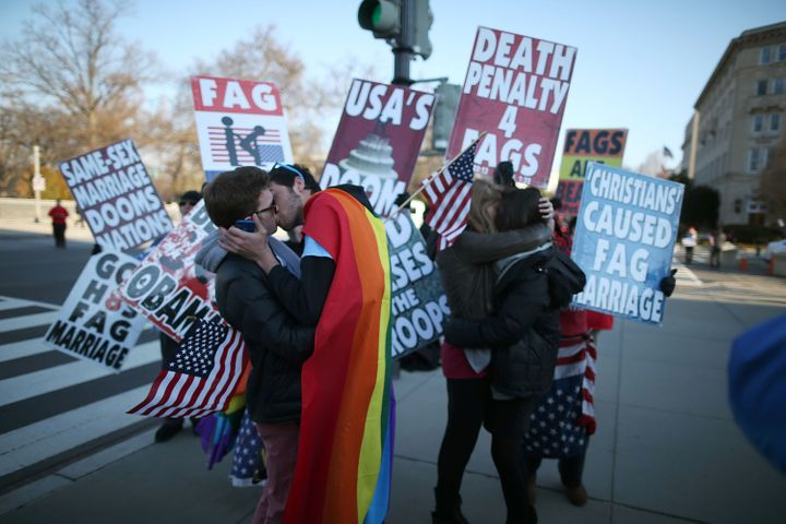 WASHINGTON, DC - MARCH 27: Two same sex couples kiss in front of Westboro Baptist Church protesters, at the U.S. Supreme Cour