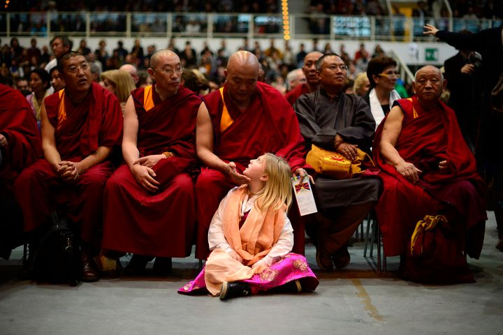 A girl sits by buddhist monks during a public meeting of the Tibetan spiitual leader, the Dalai Lama, after he was awarded th