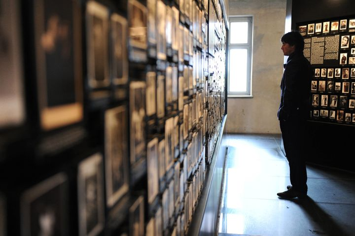OSWIECIM, POLAND - JUNE 01:  German coach Joachim Loew looks at personal photos that belonged to incoming prisoners in the so