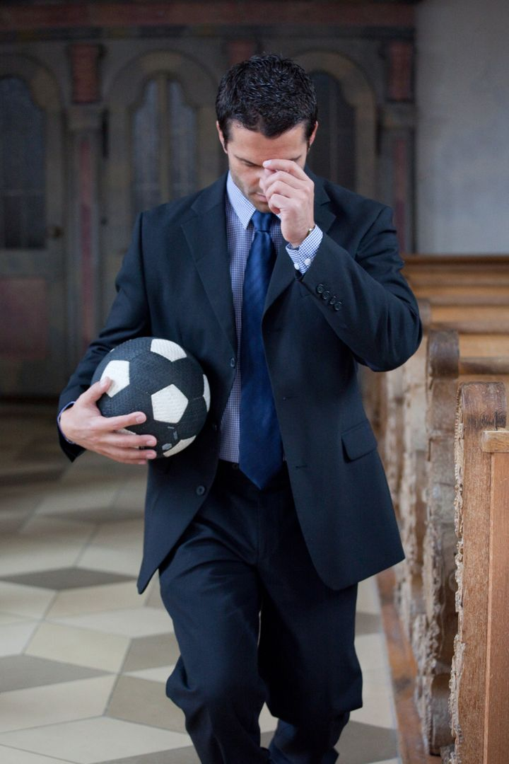 Man with football in prayer