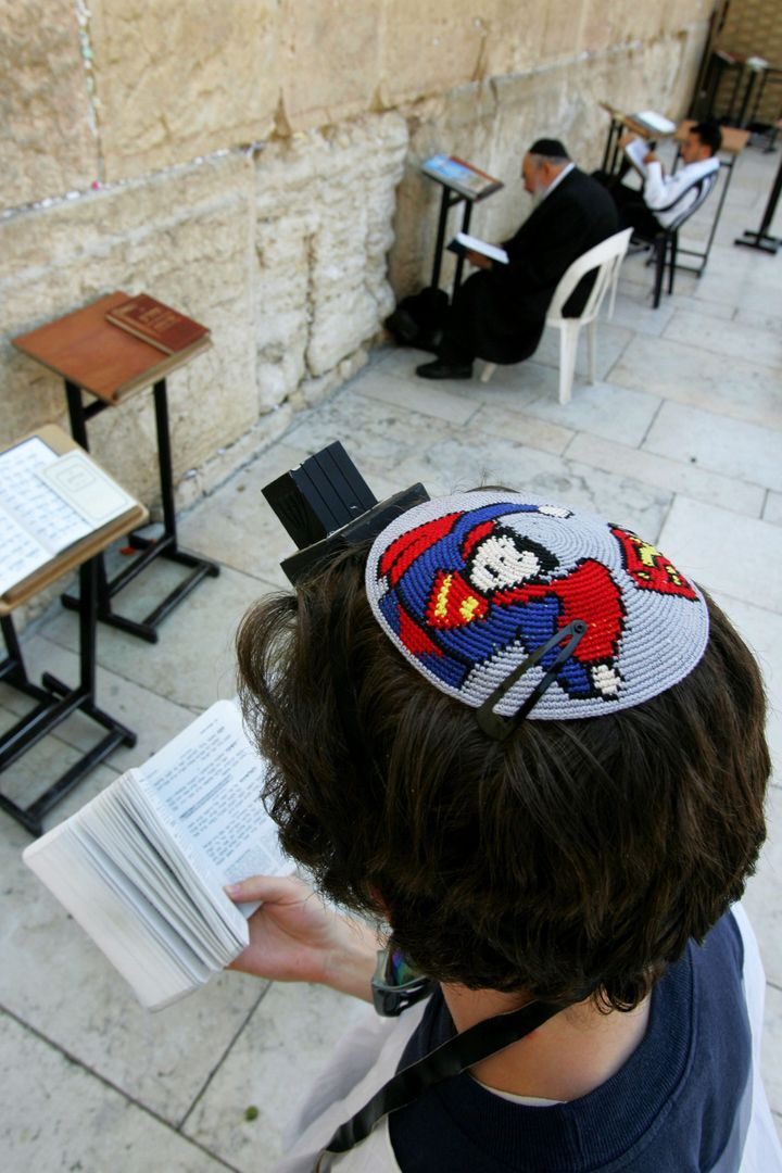 JERUSALEM - JUNE 15:  A religious Jew wears a yarmulka, a Jewish skullcap, with a Superman design as he prays at the Western