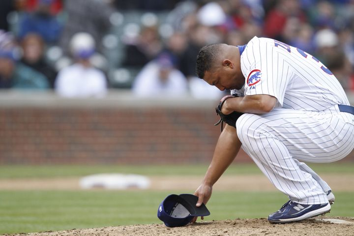CHICAGO, IL - MAY 12: Carlos Zambrano #38 of the Chicago Cubs kneels to pray before pitching against the Florida Marlins at W