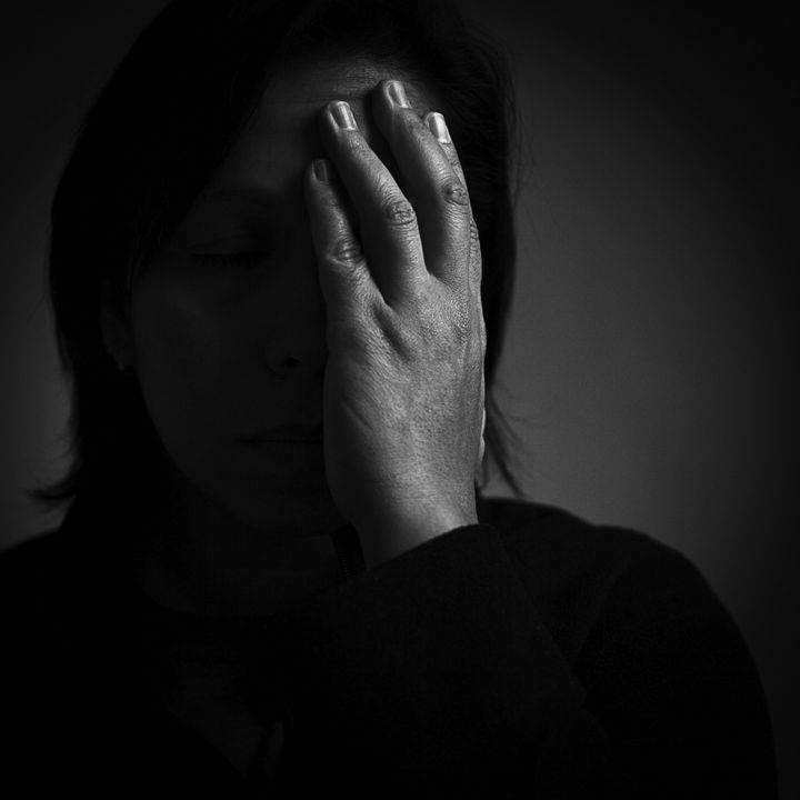 Dark female portrait with hand covering half of face.