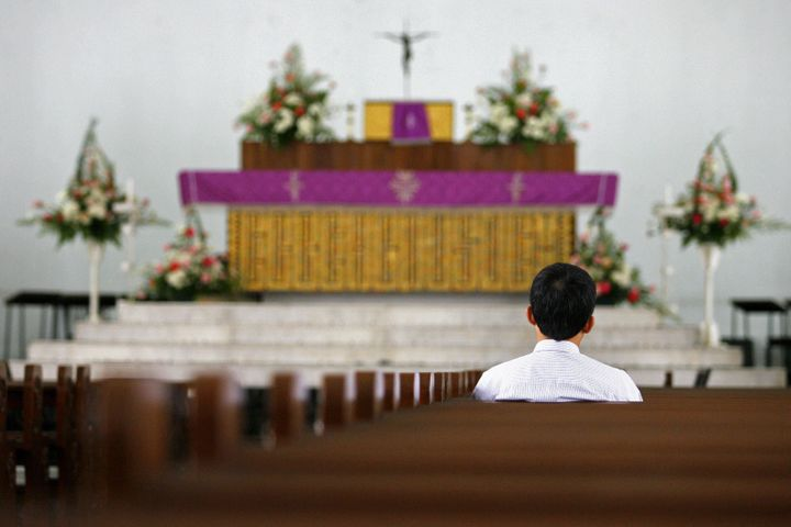Kuala Lumpur, MALAYSIA:  A lone churchgoer prays among empty benches at a cathedral in downtown Kuala Lumpur, 20 December 200