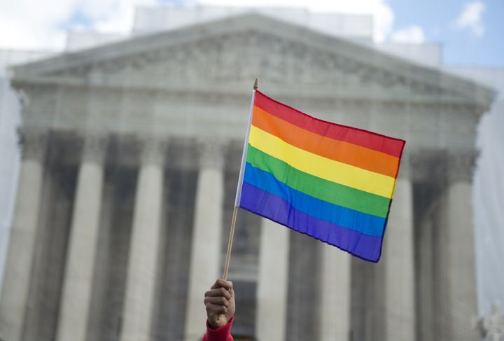 A same-sex marriage supporter waves a rainbow flag in front of the US Supreme Court on March 26, 2013 in Washington, DC, as t