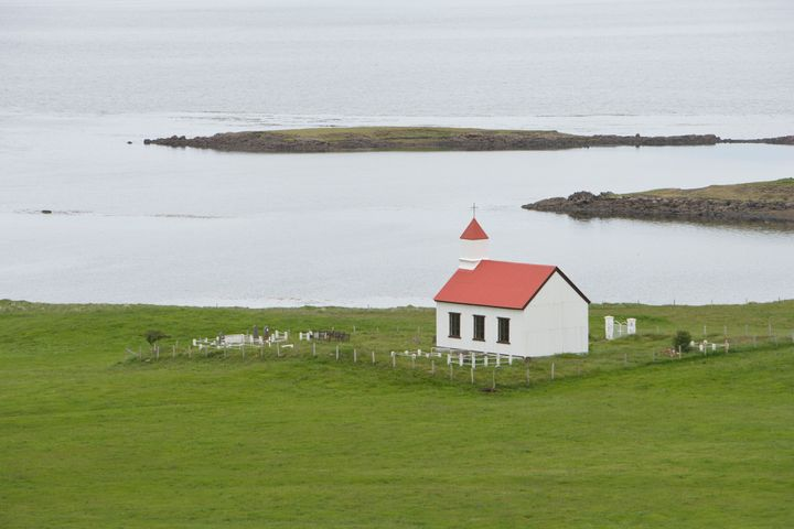 Small, white church at the edge of a body of water, surrounded by green grass, Iceland.