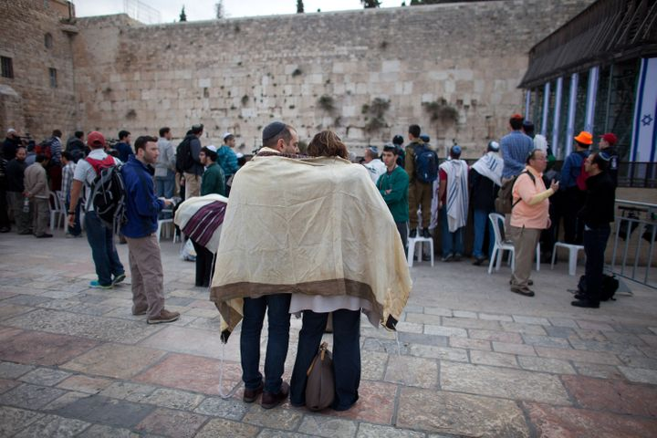 JERUSALEM, ISRAEL - APRIL 11:  (ISRAEL OUT) A couple covered with a 'Tallit' (traditional Jewish prayer shawl) pray as member