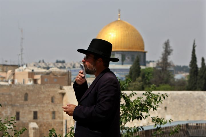 An Ultra-Orthodox Jewish man prays near the Western Wall in Jerusalem' s Old City backdropped by the Dome of the Rock Mosque,