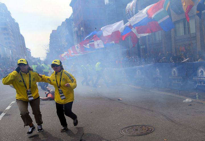BOSTON - APRIL 15: Two officials run away from the first explosion, right, on Boylston Street at the 177th Boston Marathon, A