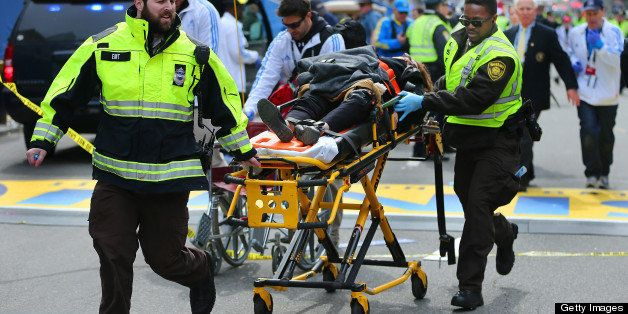 BOSTON - APRIL 15: A person who was injured in the first explosion is wheeled across the finish line of the Boston Marathon.