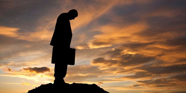 A sad and dejected businessman. Side view. Profile. Silhouette. Business concept.