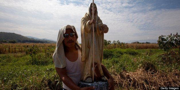OAXACA, MEXICO - NOVEMBER 2: A man carries a skeletal figure representing the folk saint known in Mexico as 'Santa Muerte' or