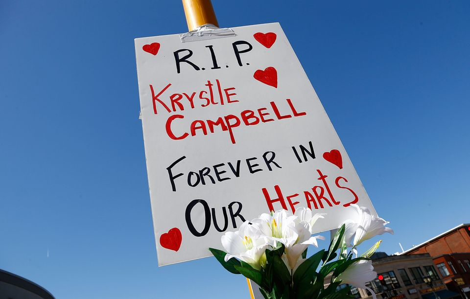 Flowers and a sign are left on a street post in Medford Square in remembrance of Krystle Campbell, 29, of Medford, Mass., who