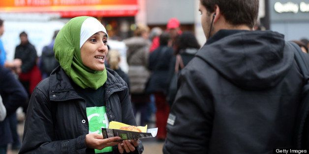 A member (L) of the Collective against Islamophobia in France (CCIF) distributes French pastries, called 'pain au chocolat,'