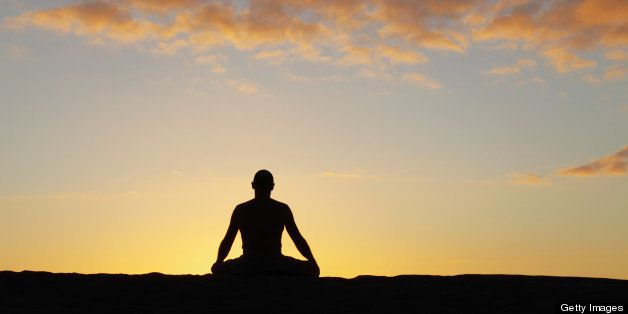 silhouette of a meditating man against sunset sky