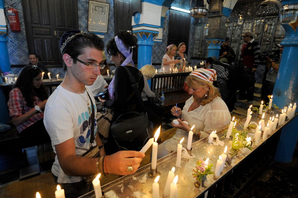 A Tunisian Jewish man lights a candle during the first day of a pilgrimage at the Ghriba synagogue in Djerba on May 9, 2012.