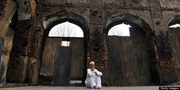 A Kashmiri Muslim man looks at the ruins of a revered 200-year old sufi shrine in downtown Srinagar on July 5,2012, which was