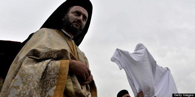Greek Orthodox priests cover the body of the Christ with a white cloth during the Apokathelosis on April 2, 2010, marking the
