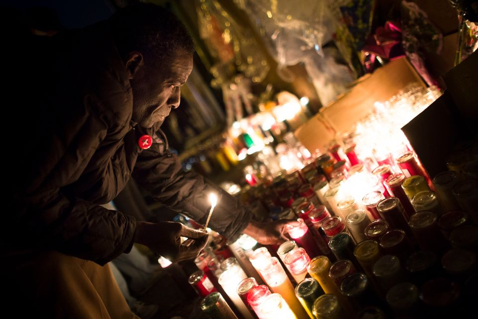 "Evan Brown, 53, lights candles during a vigil held for Kimani ""Kiki"" Gray in the East Flatbush neighborhood of Brooklyn, Wedn"