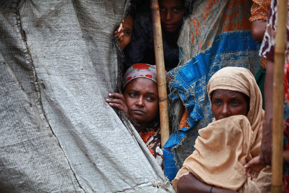 Muslim Rohingya women sit inside a tent at Mansi Internally Displaced Persons (IDP) camp in Sittwe on May 14, 2013. Boats car