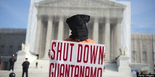 A protestor wears an orange prison jump suit and black hood on their head during protests against holding detainees at the mi