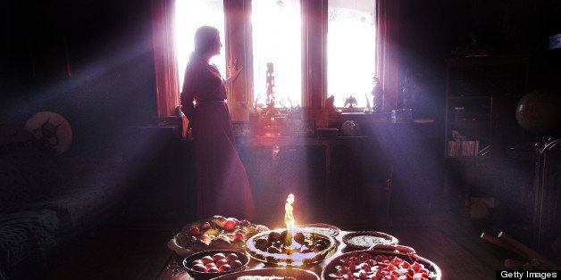 WICCAN COOKING01-03/18/01-Tmarra James is silhouetted by the afternoon light. In the foreground are examples of Wiccan cookin