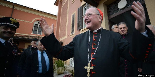 US cardinal and head of New York archdiocese, Timothy Michael Dolan (R), waves after leading a mass at the Nostra Signora di