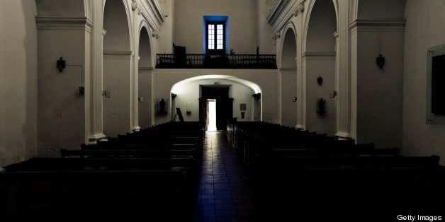 Light falling through open door and window in old ancient church in Uruguay, South America.