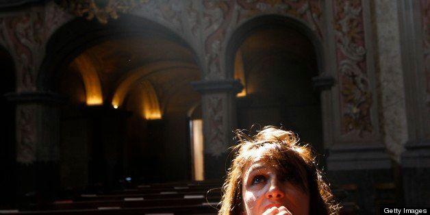 Austria, Lower Austria, Herzogenburg. The baroque church of the abbey of Herzogenburg.  Woman praying.  Austria.
