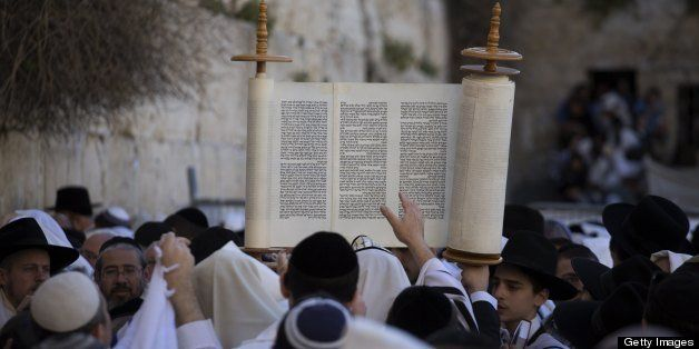 A Jewish man raises Torah scrolls during the Cohanim prayer (priest's blessing) during the Pesach (Passover) holiday at the W