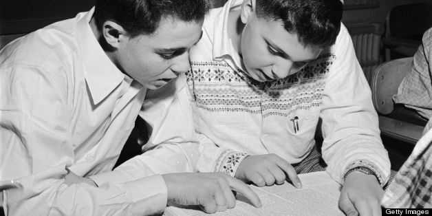 circa 1950:  Jewish students celebrating the spring festival of Purim (Lots) by reading the Megillah in the synagogue.  (Phot